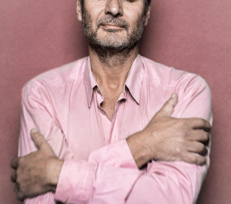Man in roze shirt met armen over elkaar