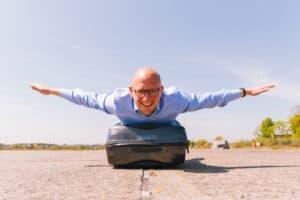 Liggend op een koffer alsof je vliegt als vliegende start voor ondernemers