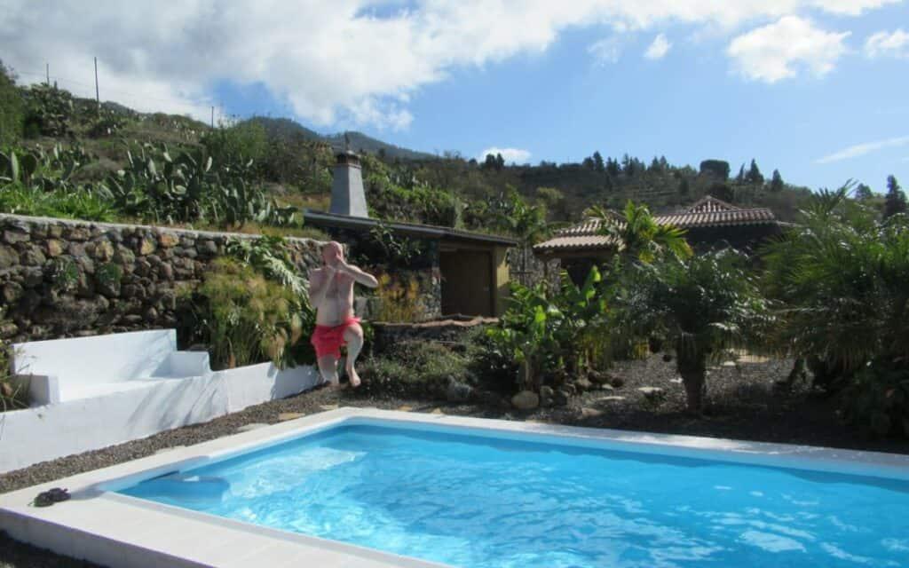vakantieomgeving waarbij man in zwembad springt