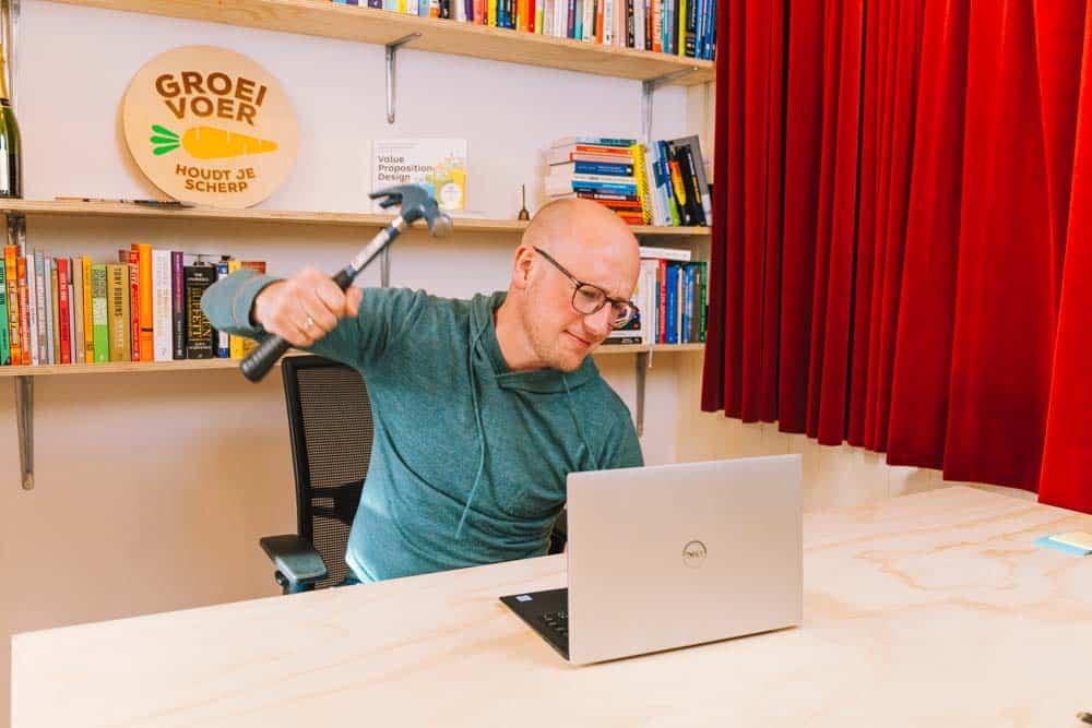 Gerhard te Velde die met een hamer op zijn laptop gaat slaan